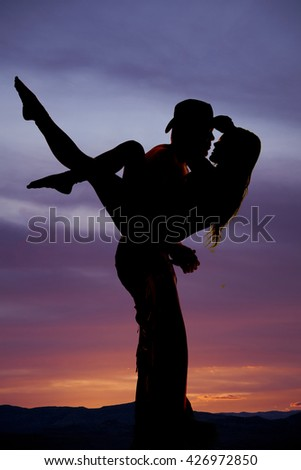 A silhouette of a cowboy holding on to his woman getting ready to kiss. - stock photo