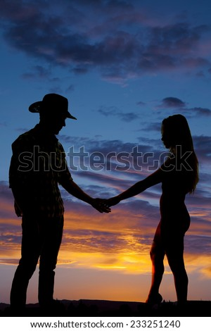 A silhouette of a cowboy holding on to his woman's hand in the outdoors. - stock photo