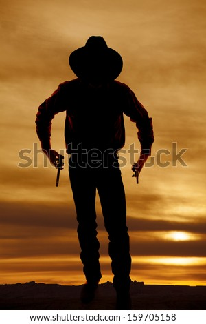 A silhouette of a cowboy holding onto his pistols. - stock photo