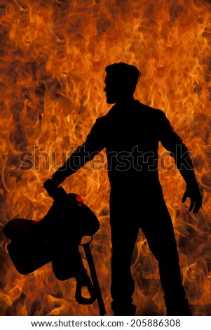 a silhouette of a cowboy holding onto his saddle with a fire background. - stock photo