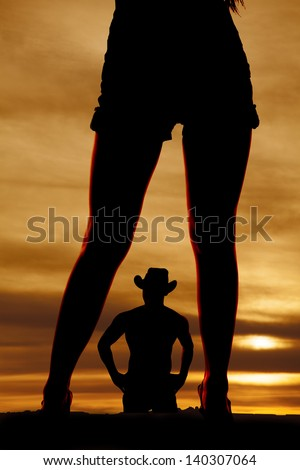 a silhouette of a cowboy in the middle of woman's legs. - stock photo