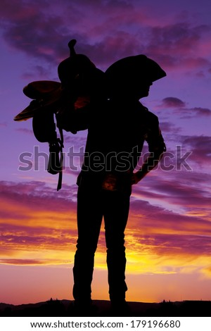 A silhouette of a cowboy in the sunset with a saddle on his shoulder. - stock photo