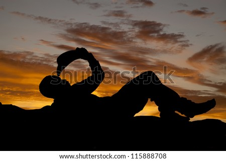 a silhouette of a  cowboy laying down on the ground with a beautiful sky behind him. - stock photo