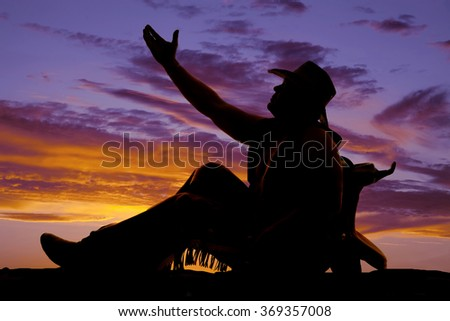 a silhouette of a cowboy leaning back against his saddle reaching up. - stock photo