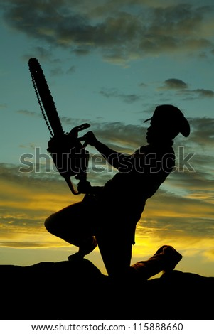 a silhouette of a cowboy on his knee holding on to his chainsaw. - stock photo