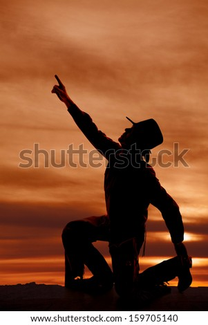a silhouette of a cowboy reaching his arm up to the sky. - stock photo