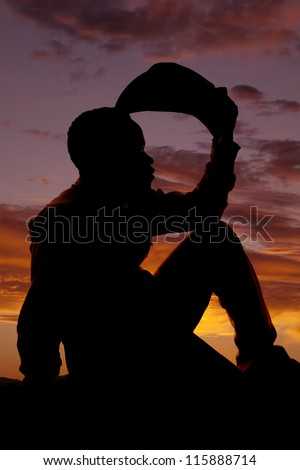 a silhouette of a cowboy sitting and holding his hat thinking