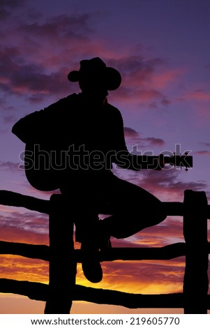 A silhouette of a cowboy sitting on a fence playing his guitar. - stock photo
