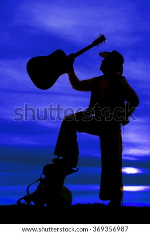 A silhouette of a cowboy standing up on a saddle with his guitar in the air.