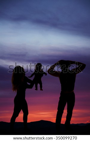 A silhouette of a cowboy standing with his woman handing over their child.