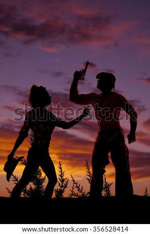 A silhouette of a cowboy with a gun and his cowgirl reaching out to him. - stock photo