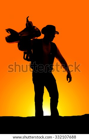 A silhouette of a cowboy with a saddle on his shoulder looking down.