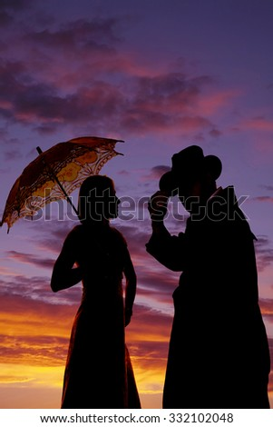 A silhouette of a cowboy with his lady, she is holding on to an umbrella.