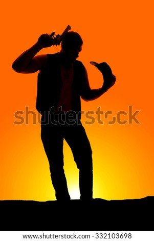A silhouette of a cowboy with his western hat off his head, and a pistol by his head. - stock photo