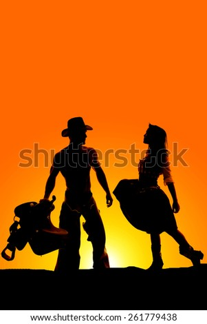 a silhouette of a cowgirl getting close to her cowboy, who is holding on to his saddle. - stock photo