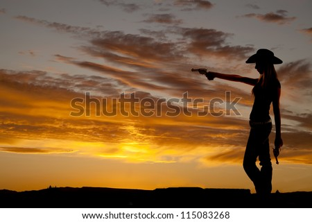 a silhouette of a cowgirl holding on to her guns pointing it at something - stock photo