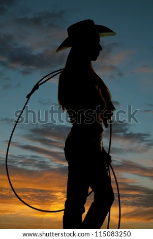 A silhouette of a cowgirl holding on to her rope. - stock photo