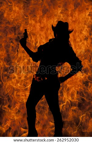 a silhouette of a cowgirl holding up her pistol in the air, with her hand on her hip - stock photo