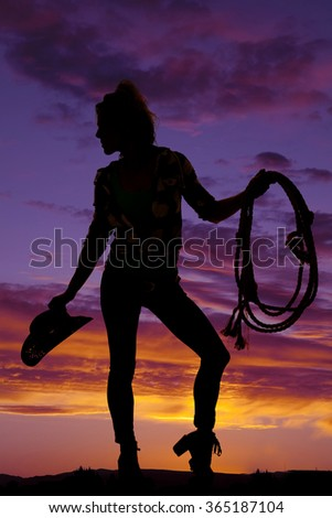 a silhouette of a cowgirl in the outdoors holding on to her western rope and hat. - stock photo