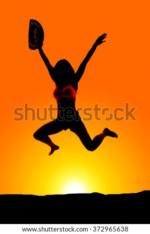 A silhouette of a cowgirl jumping with her hat in her hand. - stock photo