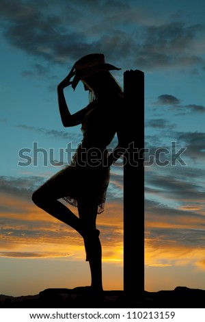 A silhouette of a cowgirl leaning back on a post holding onto her hat with a colorful sky behind her.