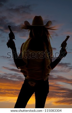 A silhouette of a cowgirl pointing her pistols up in the sky. - stock photo