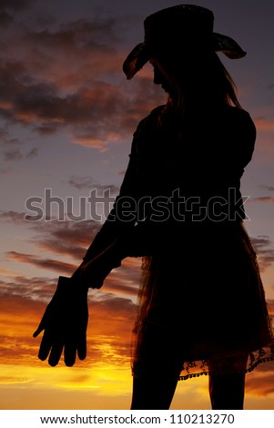 A silhouette of a cowgirl putting on her gloves with a beautiful sunset in the background. - stock photo