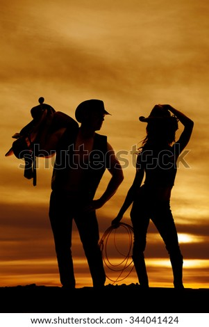 a silhouette of a cowgirl standing next to her cowboy holding on to a rope.