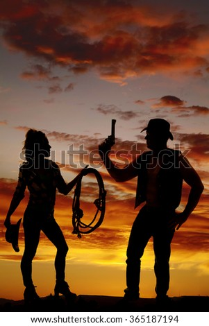 A silhouette of a cowgirl standing next to her cowboy with her rope and hat, he is holding on to a pistol.