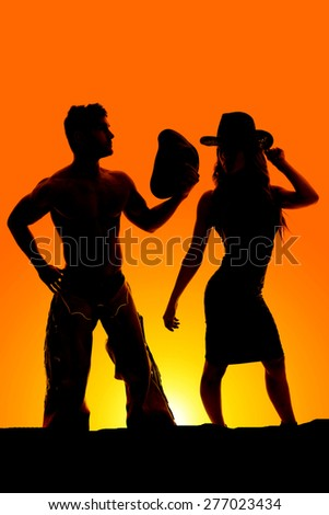A silhouette of a cowgirl with her cowboy in the outdoors - stock photo