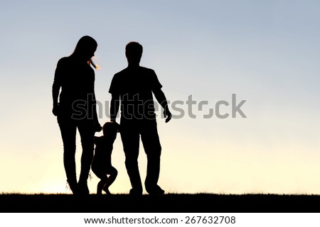 A silhouette of a family of three people, including mother, father, and young child are playing around while walking outside at sunset. - stock photo