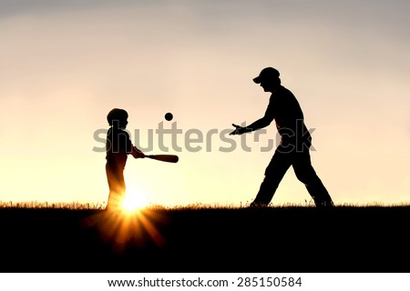 A silhouette of a father and his young child playing baseball outside, isolated against the sunsetting sky on a summer day. - stock photo