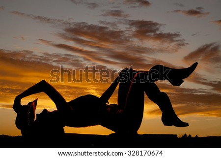 A silhouette of a girl laying back kicking up her feet. - stock photo