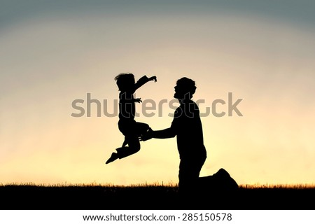 A silhouette of a happy little boy child is jumping into the loving arms of his father isolated against the sunset on a summer day. - stock photo