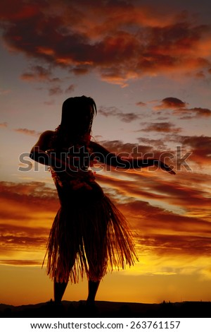a silhouette of a Hawaiian woman dancing in the outdoors.