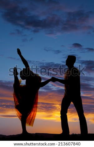 a silhouette of a man and woman dancing, he is holding her hand, while she is lifting her leg. - stock photo