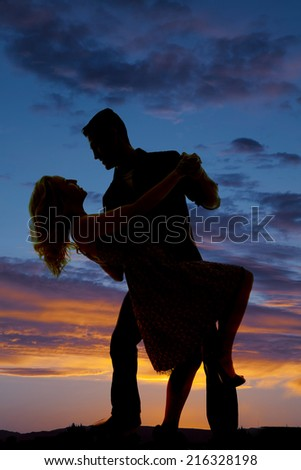 a silhouette of a man and woman dancing in the outdoors. - stock photo