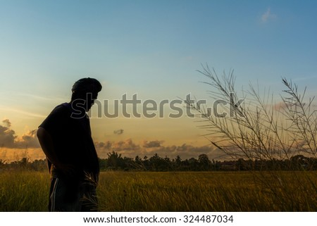 A silhouette of a man at paddy field during sunset