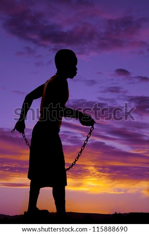 a silhouette of a man holding on to a metal chain.