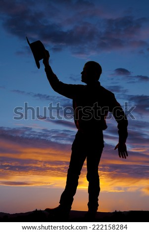 a silhouette of a man holding on to her hat. - stock photo