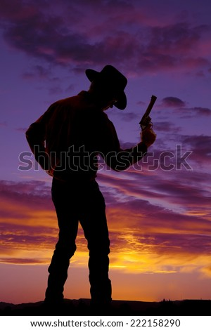 A silhouette of a man holding on to his pistol in the outdoors. - stock photo