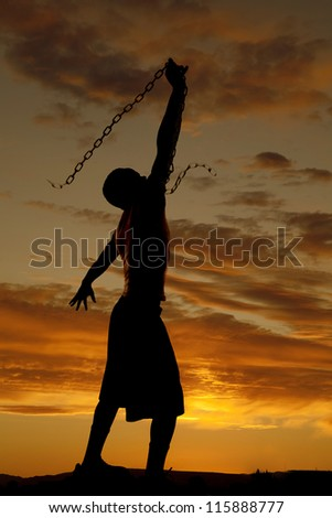 A silhouette of a man in the outdoors swinging a chain in the sky