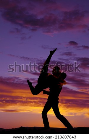 a silhouette of a man lifting up his woman doing a dancing lift.