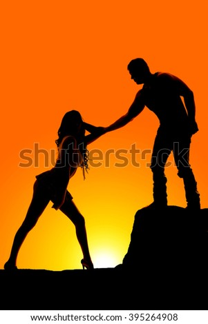 A silhouette of a man reaching out to touch his woman.