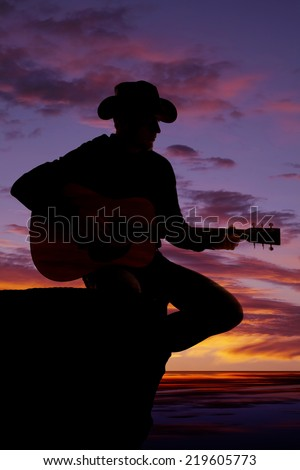 A silhouette of a man sitting on a rock ledge playing his guitar.