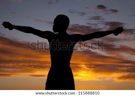 A silhouette of a man working out in the outdoors with weights - stock photo