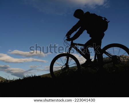 A silhouette of a mountain biker - stock photo