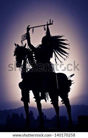 A silhouette of a Native American on a horse made from metal with distant mountains and a purple haze vignetting. - stock photo