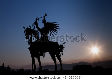 A silhouette of a Native American on a horse made from metal with eight rays emanating out from the setting sun in the distance above hazy mountains.