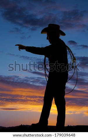 A silhouette of a older cowboy holding on to his rope. - stock photo
